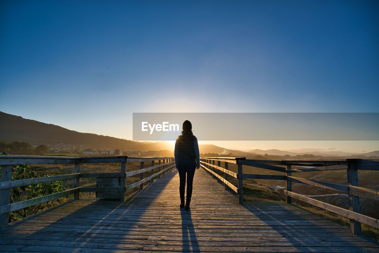 Rear view of woman standing on boardwalk against sky during sunset