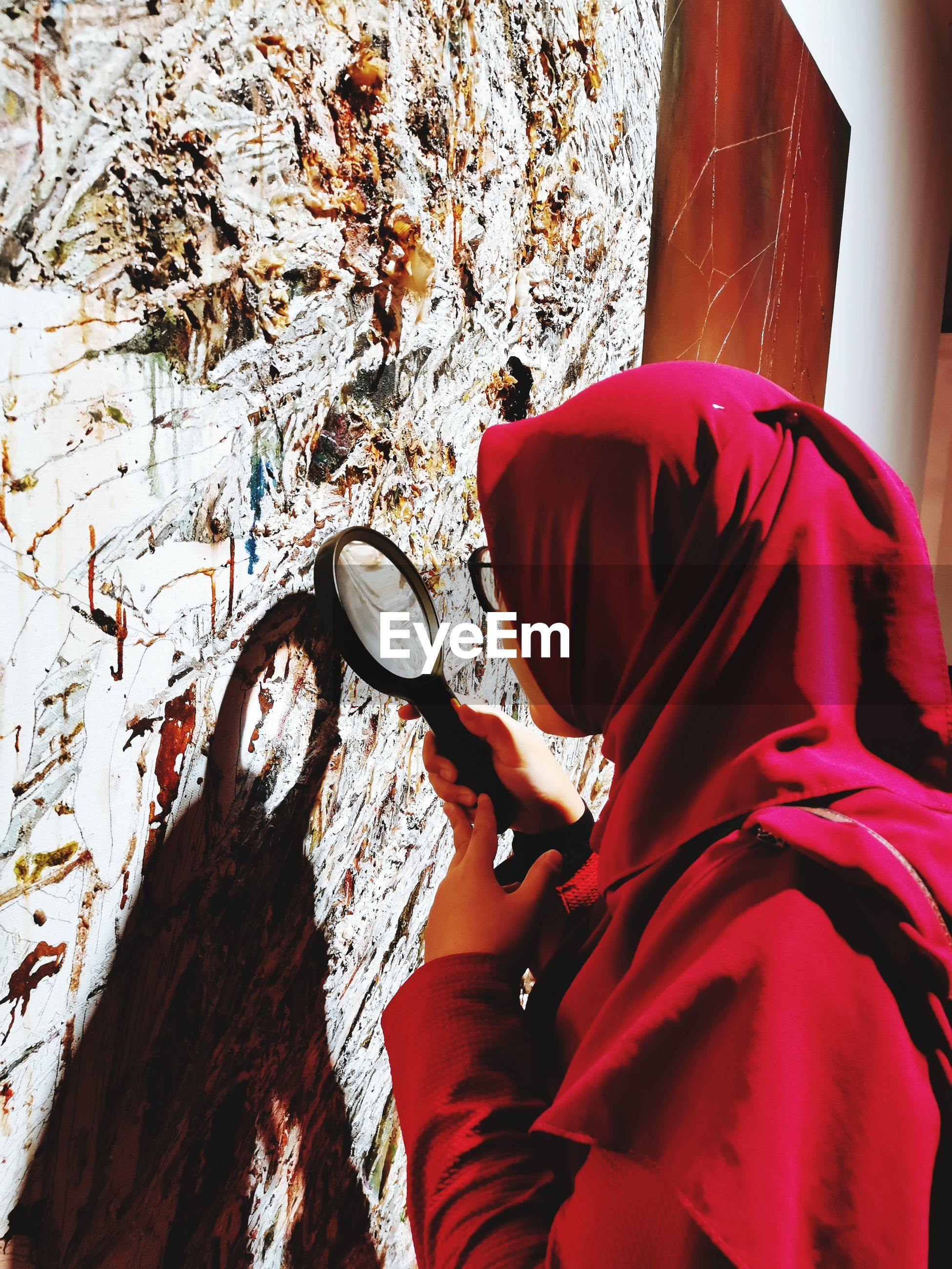 Side view of young woman wearing hijab holding magnifying glass by wall