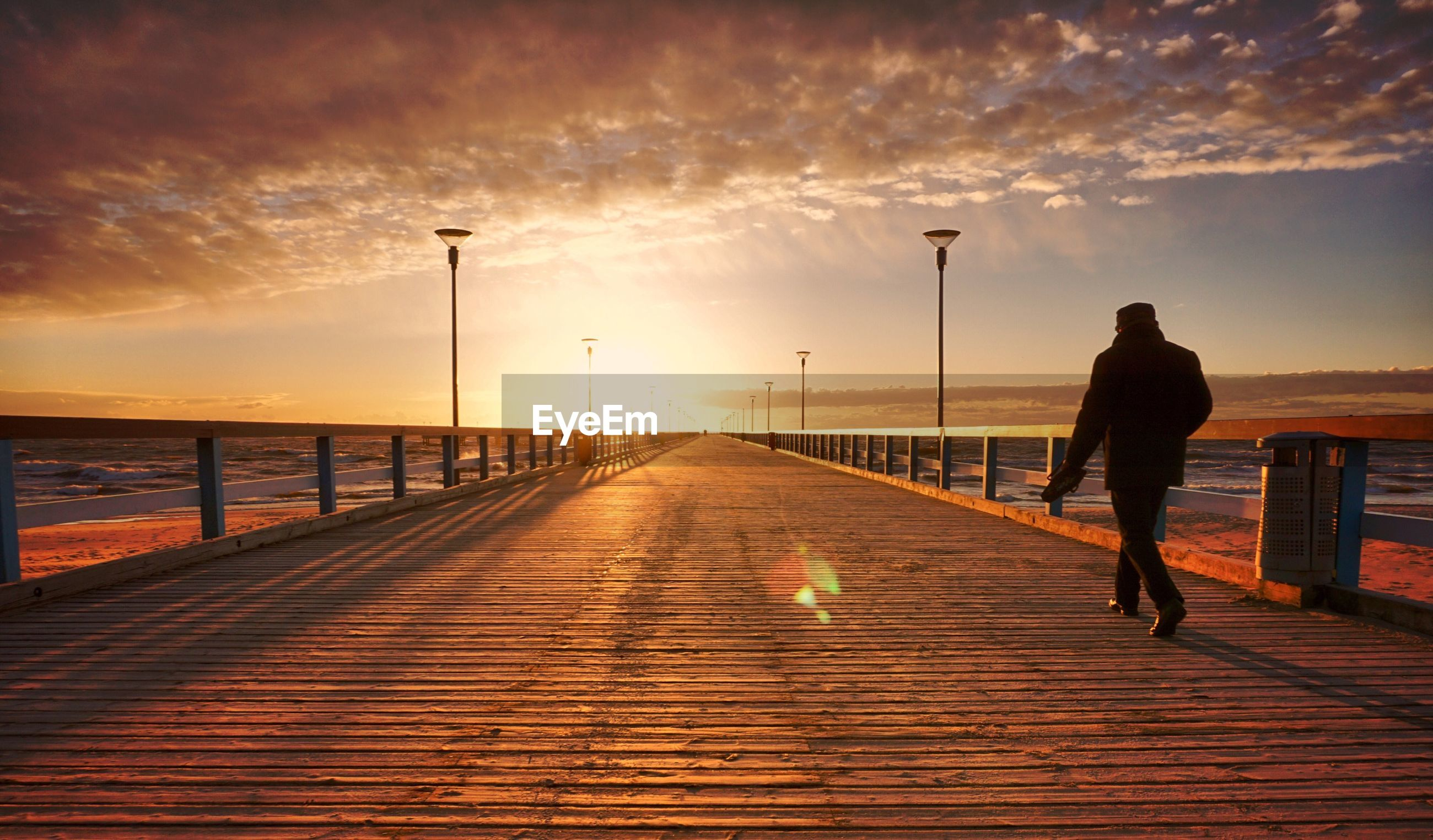 Rear view of silhouette man walking on pier against cloudy sky during sunset