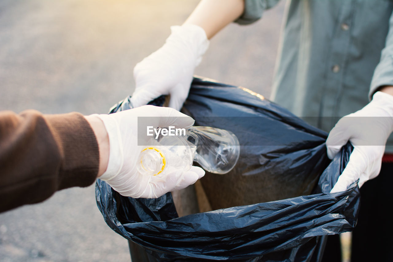 Cropped Hand Wearing Protective Glove While Putting Plastic Bottle In Bag