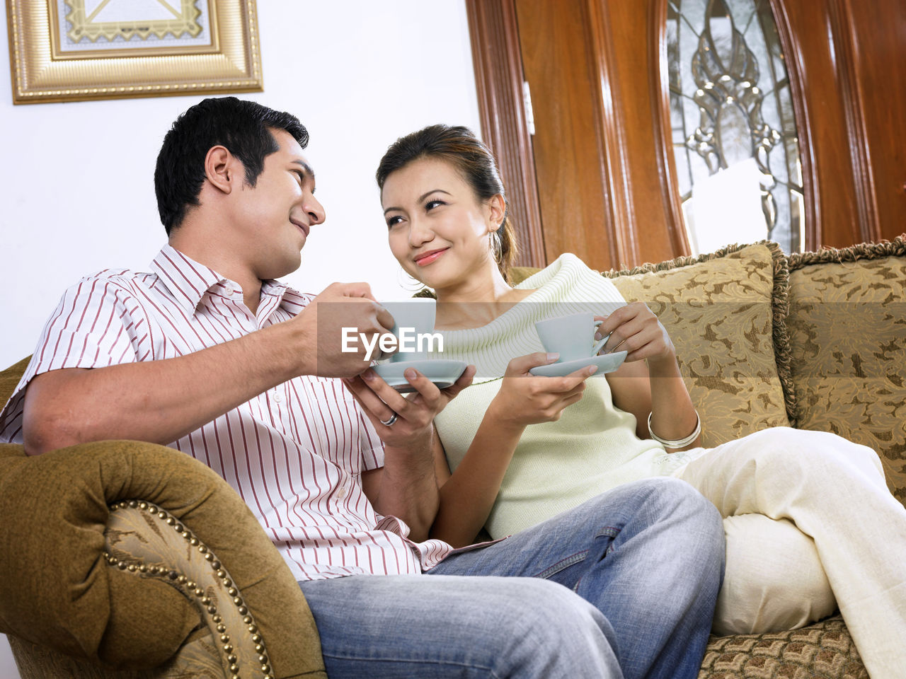 Smiling Mid Adult Couple Drinking Coffee On Sofa At Home