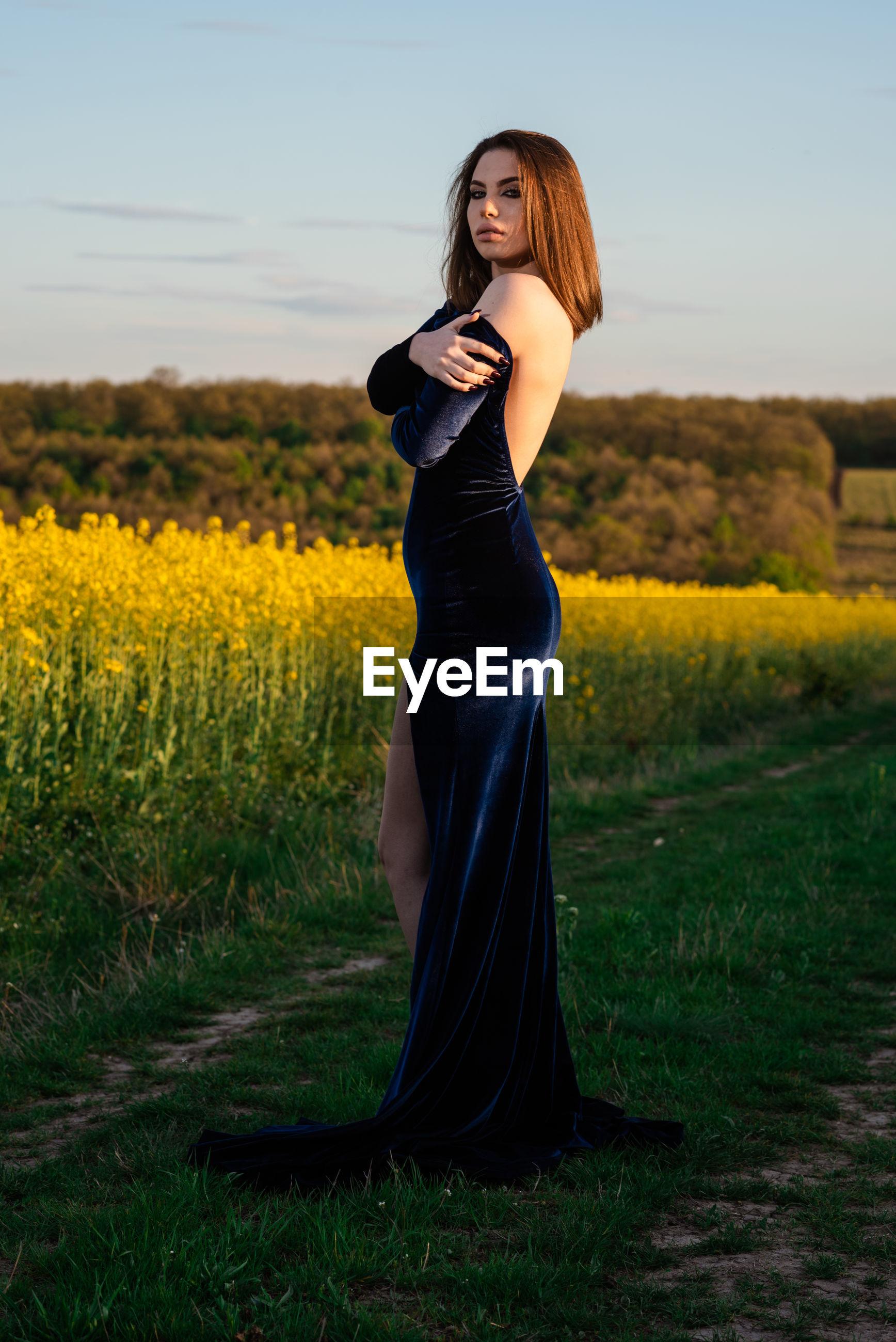 Full length portrait of woman standing on field