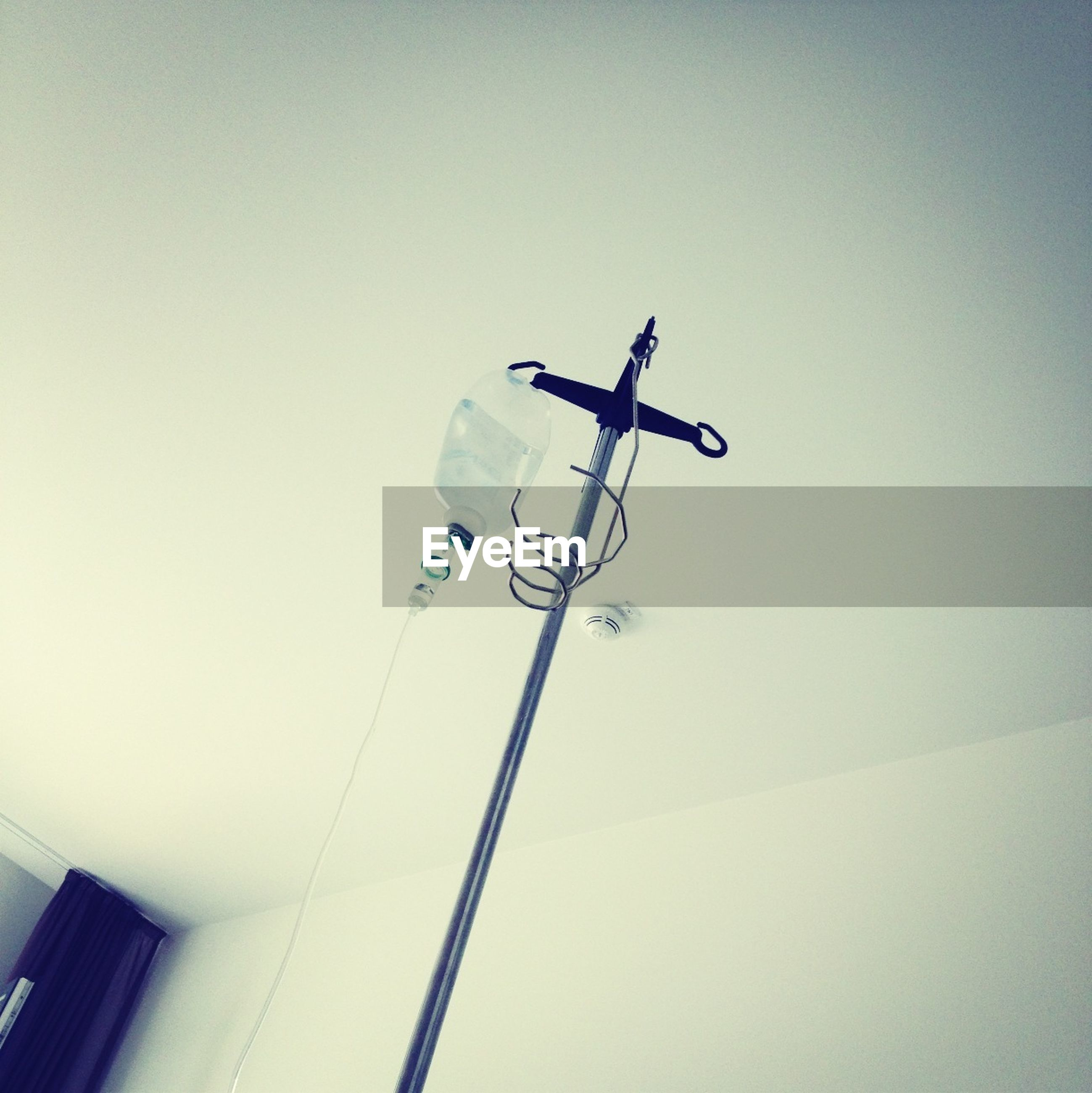 low angle view, copy space, clear sky, street light, lighting equipment, technology, built structure, day, electricity, architecture, no people, pole, outdoors, high section, sky, white color, communication, airplane, cable, mid-air