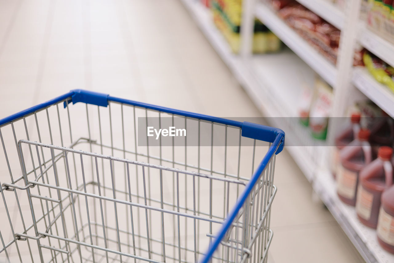 shopping cart, retail, shopping, store, supermarket, consumerism, focus on foreground, no people, indoors, selective focus, metal, close-up, trolley, empty, market, side view, absence, in a row, blue, groceries