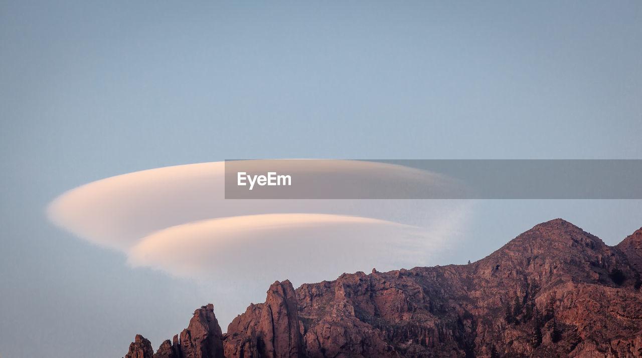 Lenticular  clouds in classic doughnut shape over a mountain ridge.