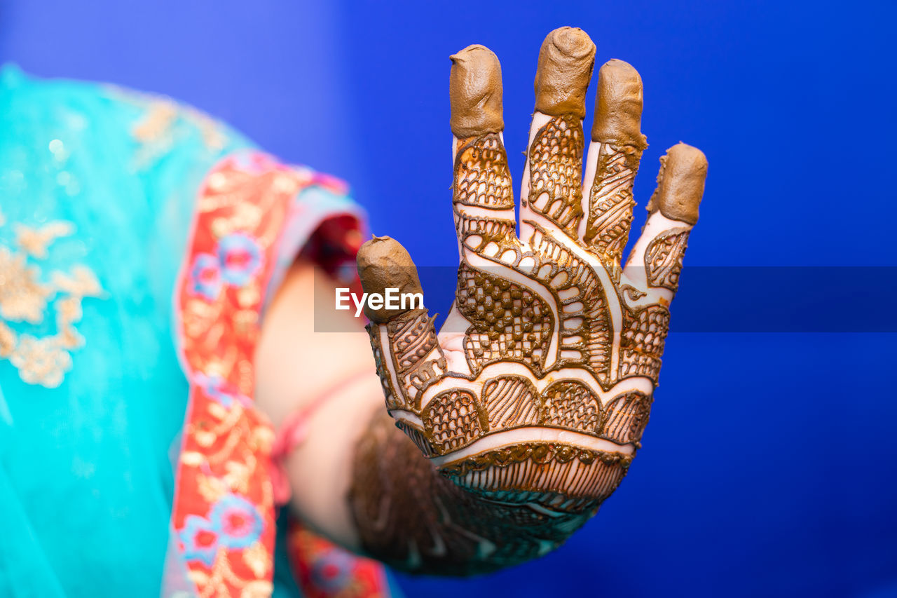 Midsection of bride with henna tattoo against blue background