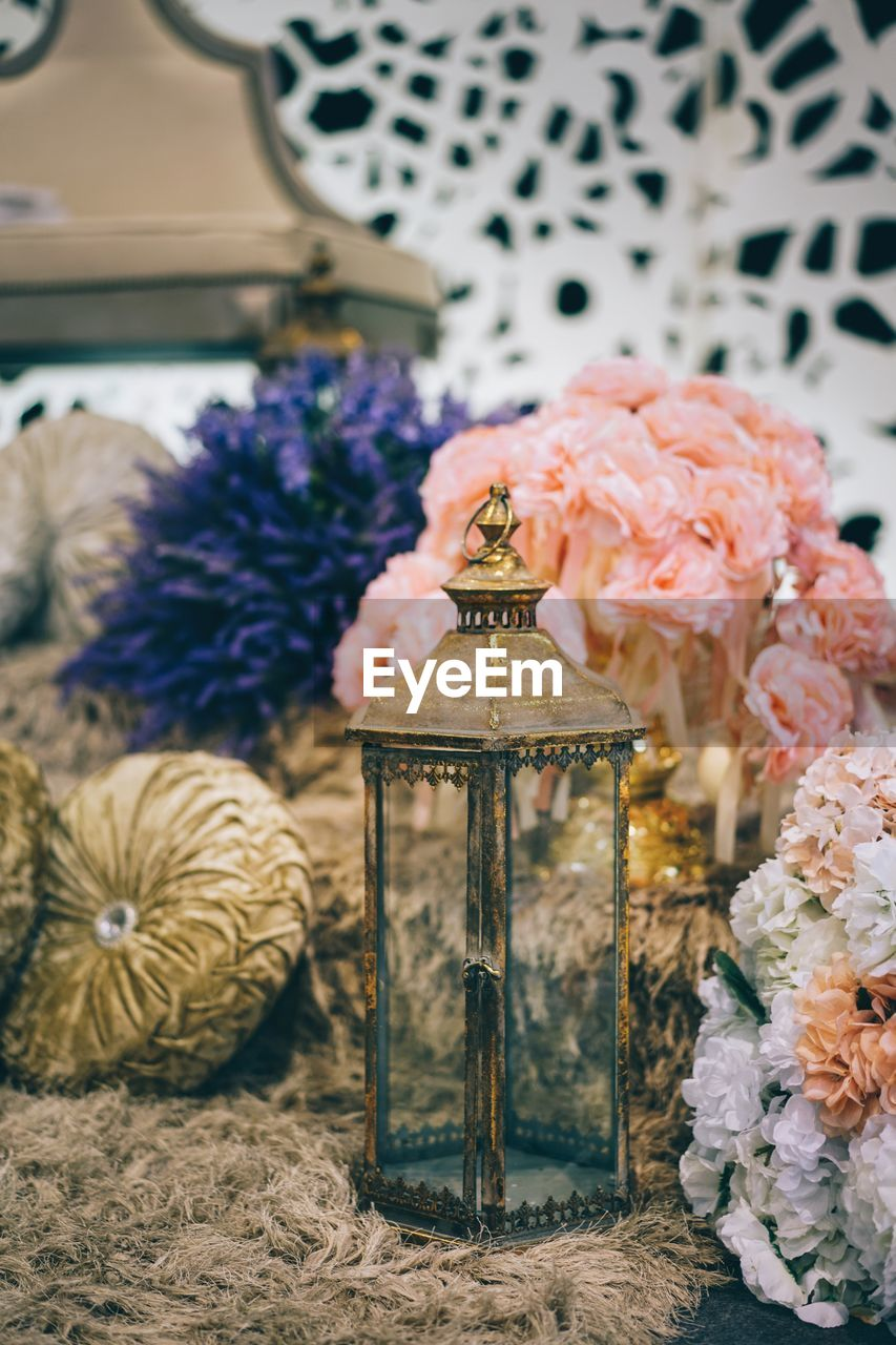 flower, flowering plant, plant, indoors, decoration, nature, no people, close-up, focus on foreground, beauty in nature, home interior, art and craft, container, freshness, table, lighting equipment, candle, fragility, vase, vulnerability, floral pattern, flower arrangement