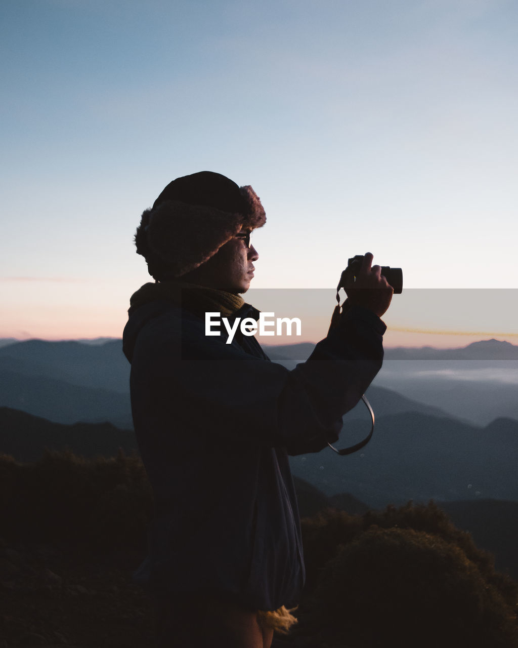 sky, photography themes, photographing, activity, camera - photographic equipment, real people, one person, standing, holding, leisure activity, technology, sunset, men, scenics - nature, beauty in nature, nature, lifestyles, mountain, side view, photographer, wireless technology, mature men, digital camera, outdoors, modern