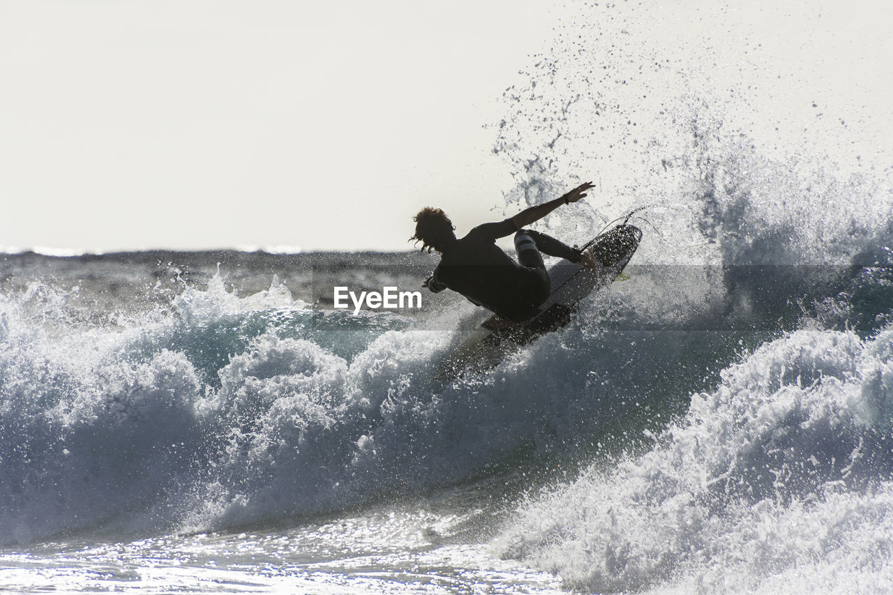 motion, water, sea, aquatic sport, wave, sport, adventure, surfing, waterfront, leisure activity, one person, lifestyles, extreme sports, nature, splashing, sky, real people, day, skill, outdoors, power in nature, horizon over water