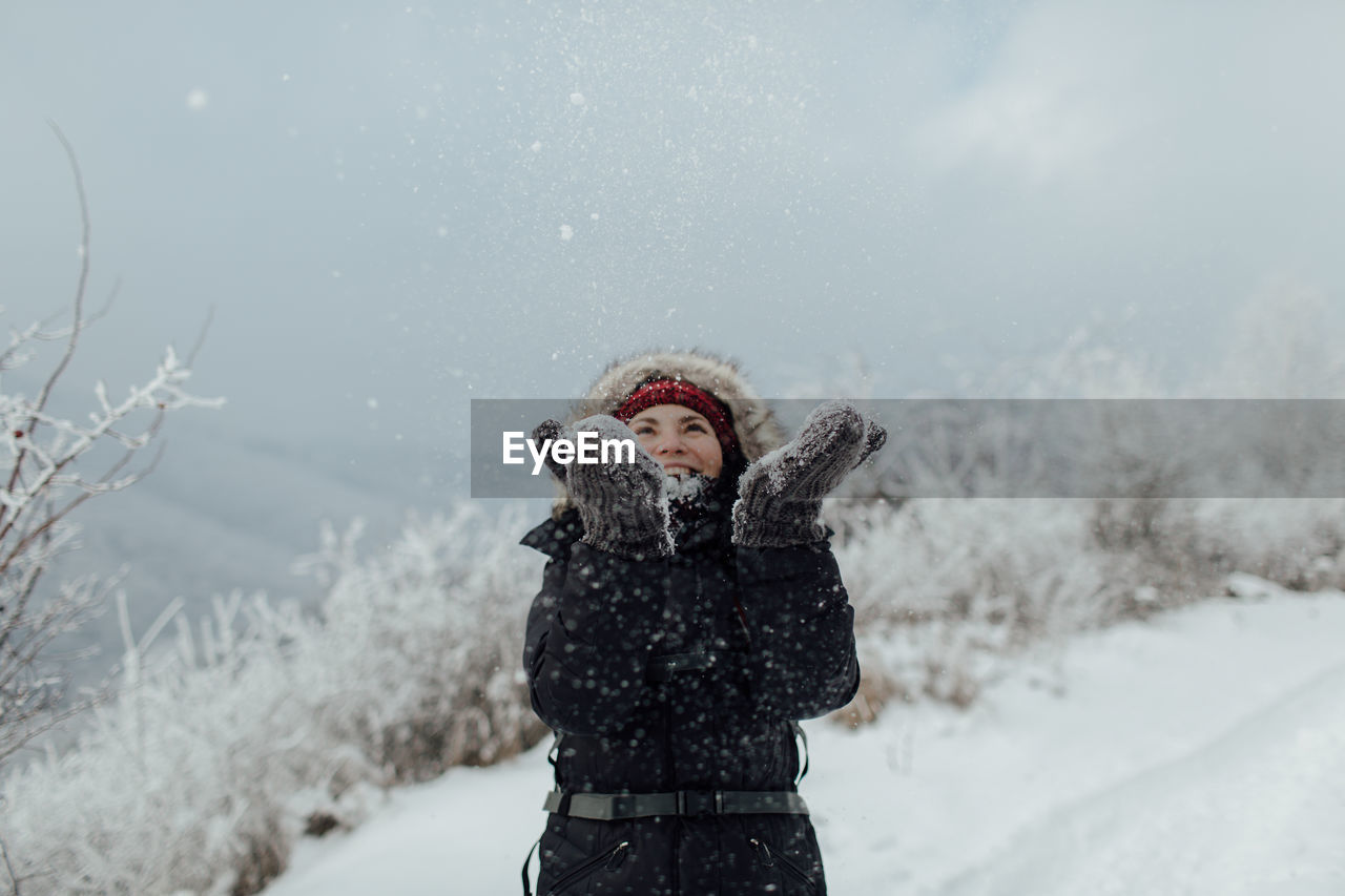 Cheerful Woman In Warm Clothing Throwing Snow While Standing On Mountain