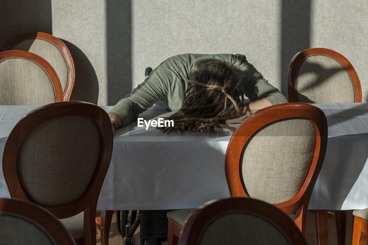 Man with dreadlocks sleeping on table