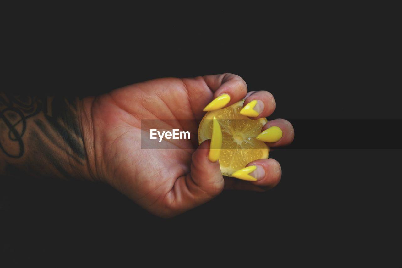 Close-Up Of Hand Holding Lemon Slice Over Black Background