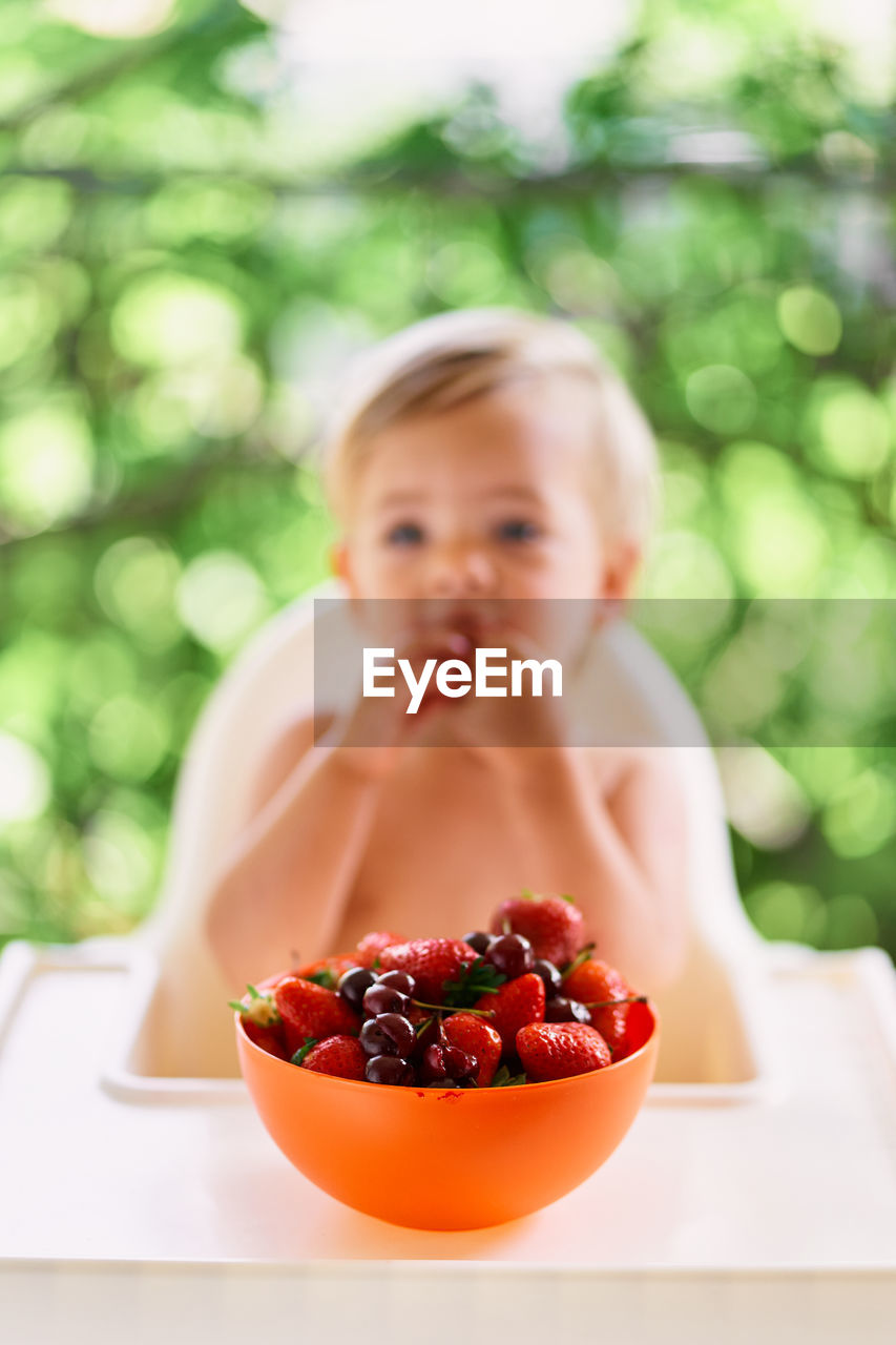Portrait of boy eating fruits in bowl