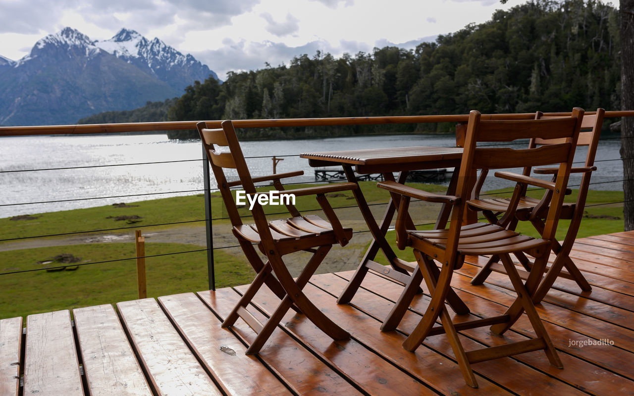 mountain, wood - material, table, seat, tree, no people, beauty in nature, plant, empty, nature, tranquility, day, tranquil scene, absence, scenics - nature, chair, water, railing, non-urban scene, lake