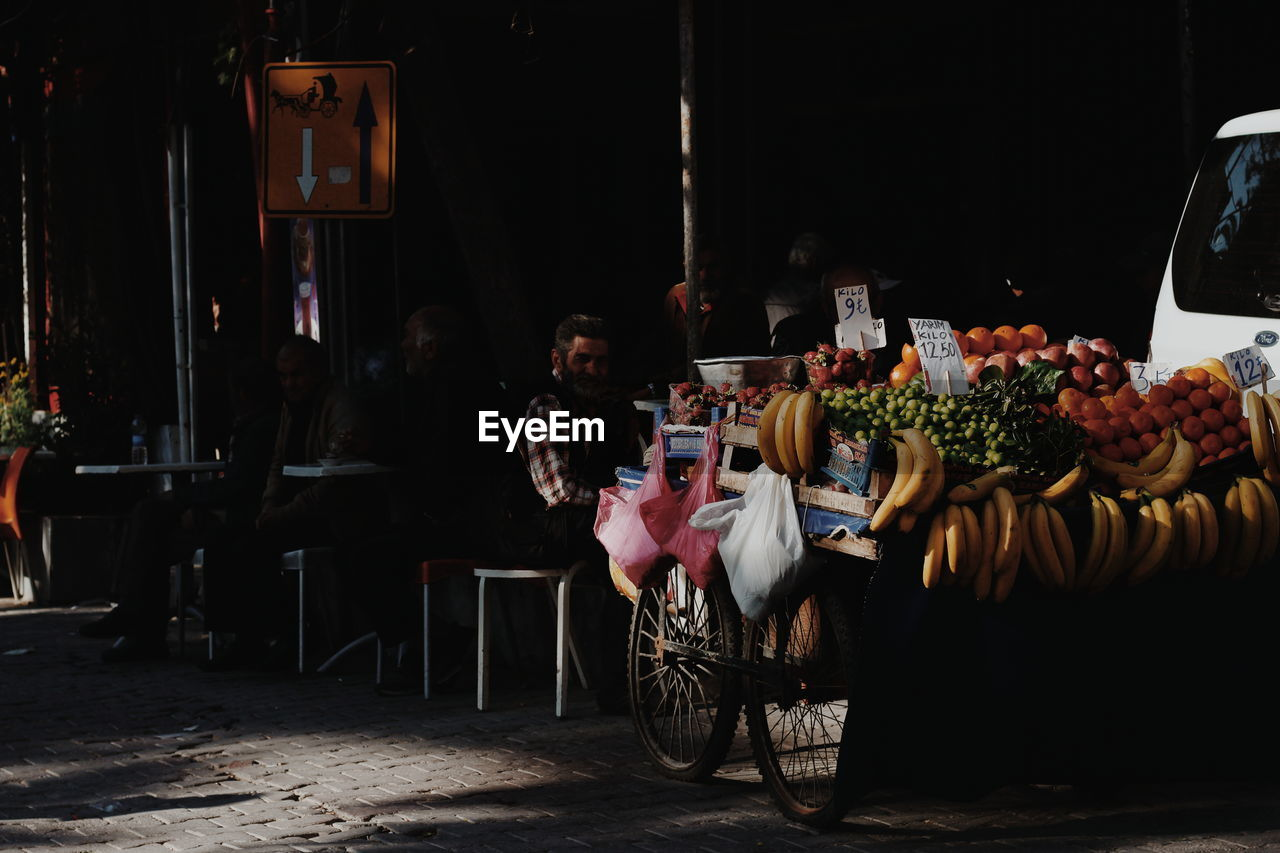 Man sitting at market stall in city