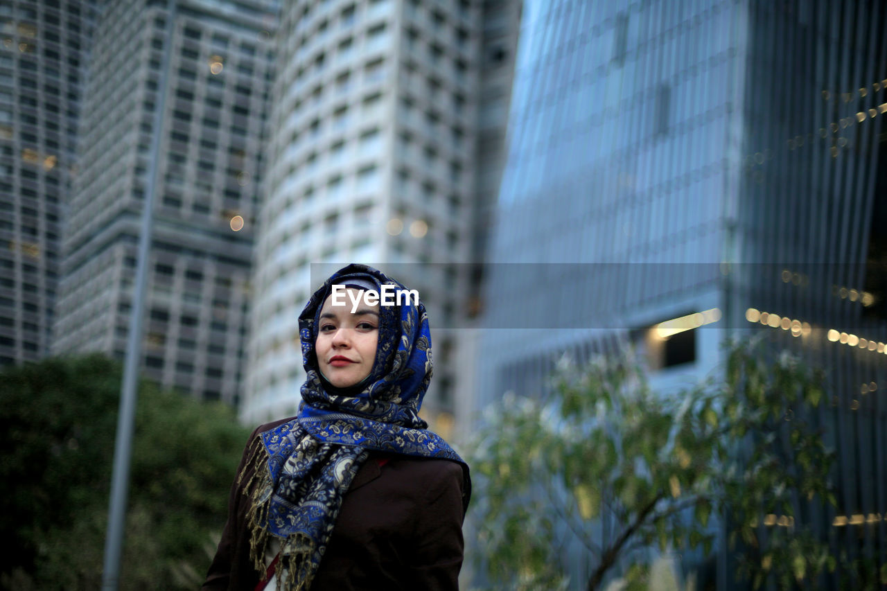 Low angle view of young woman looking away against buildings in city