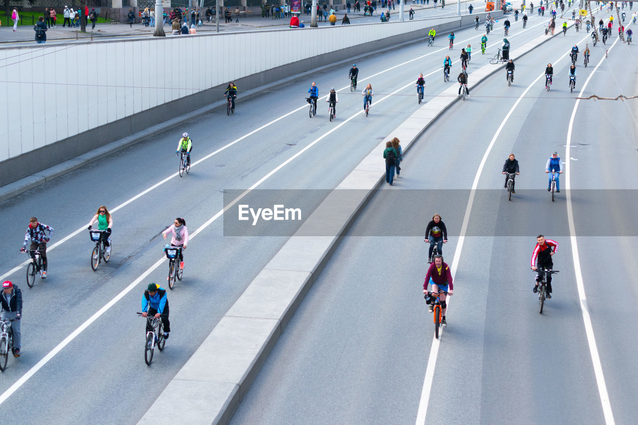 High Angle View Of People Riding Bicycle On Road In City
