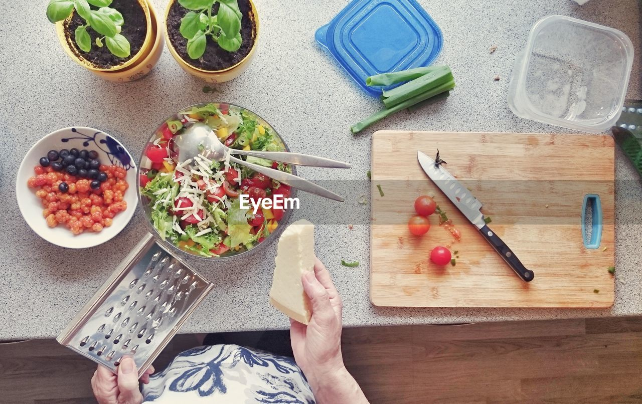 Cropped Image Of Woman Grating Cheese Over Salad In Kitchen