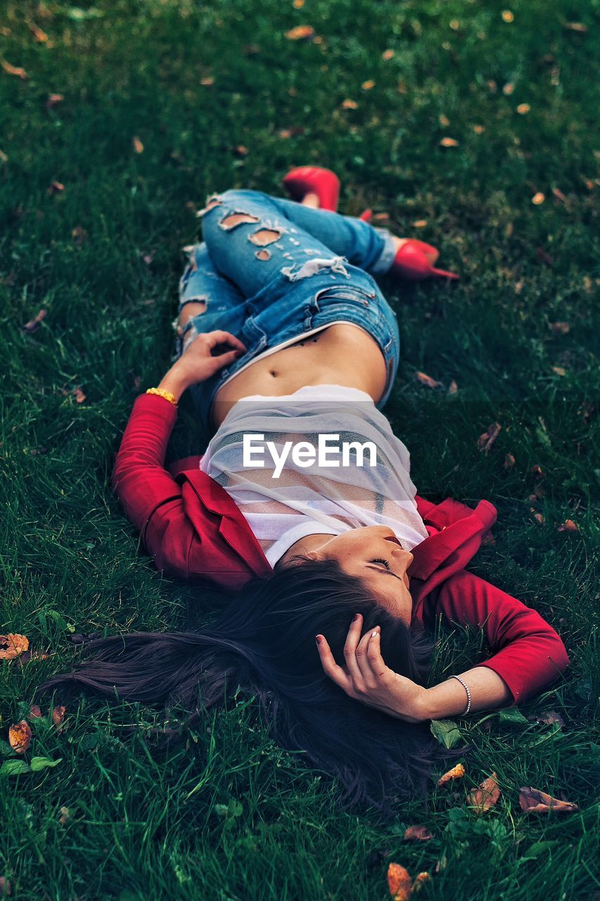 High Angle View Of Fashionable Woman Lying On Grass At Park