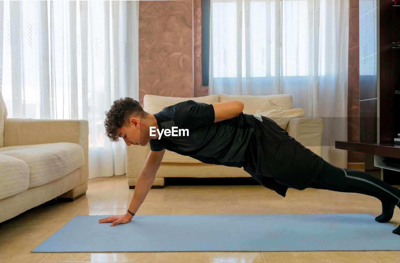 Side view of young man exercising on mat at home