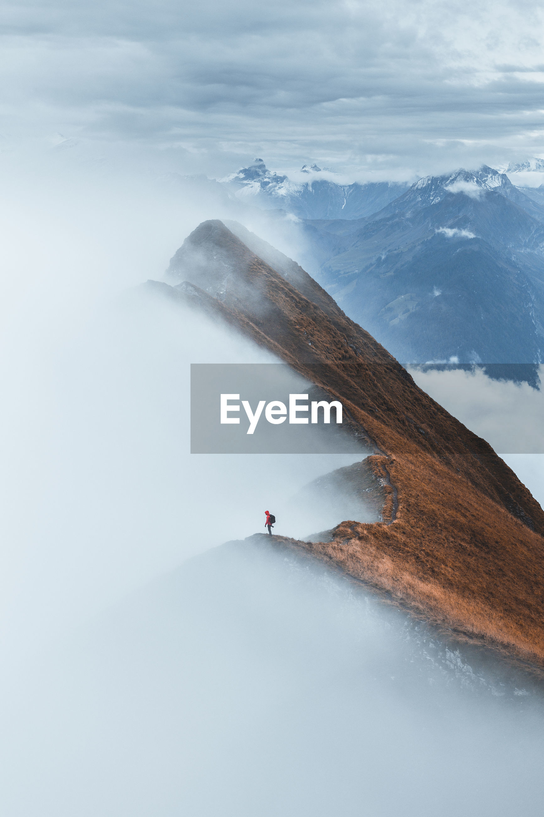 Mid distant view of man standing on mountain ridge
