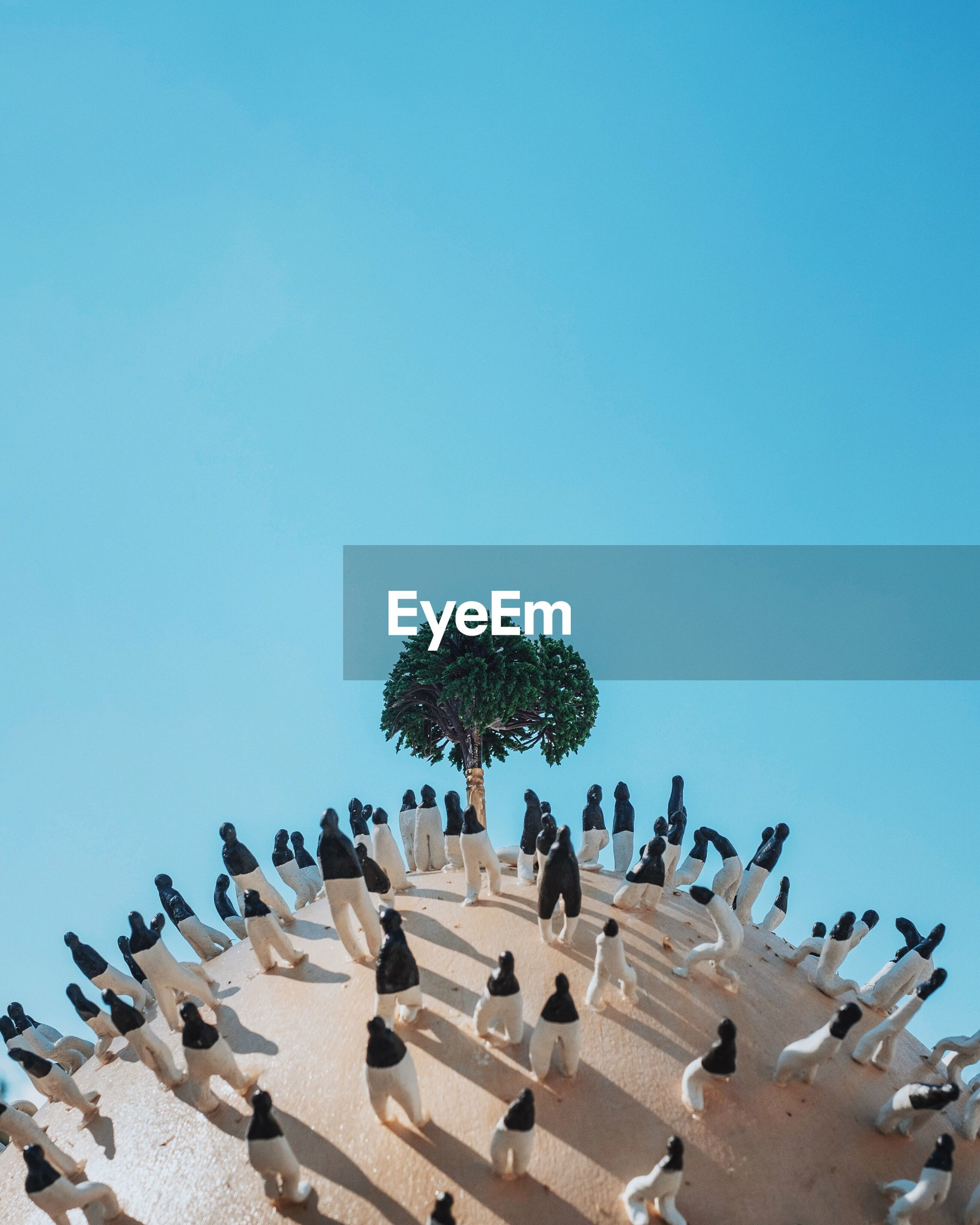 Artificial tree surrounded by figurines against clear blue sky