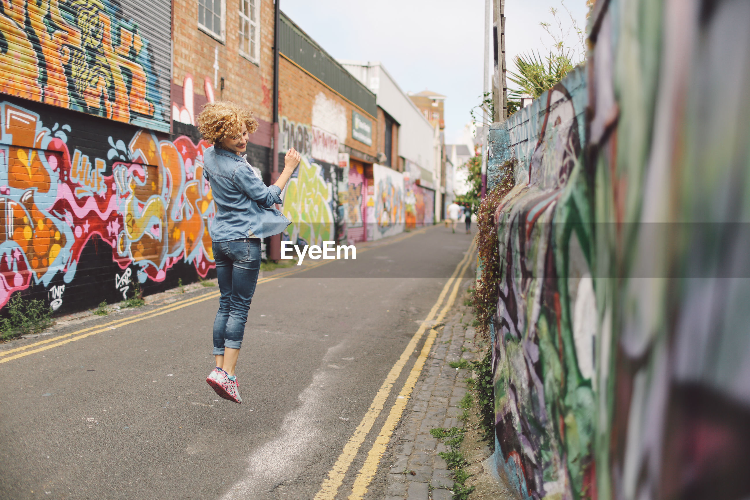 Full length of woman jumping on street
