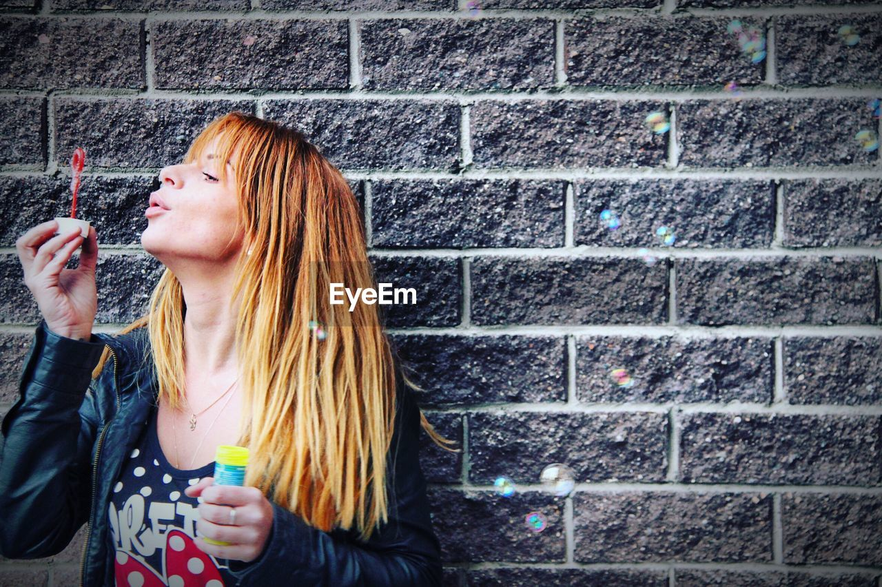 Woman blowing bubbles against brick wall