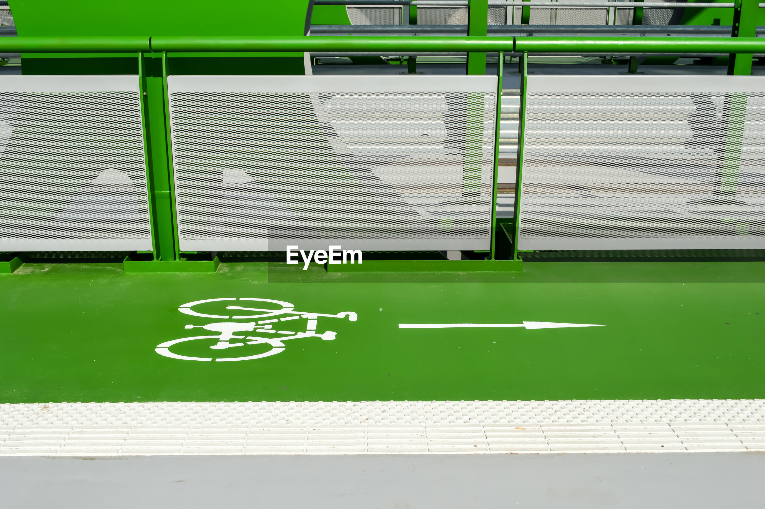 Bicycle lane on green road by railing