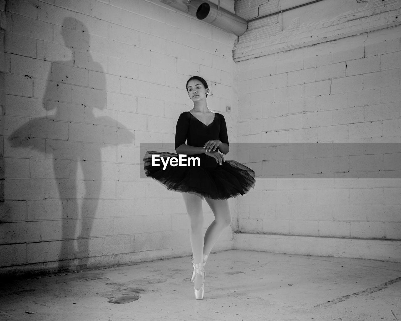 Ballerina Performing Ballet Dance Against Wall