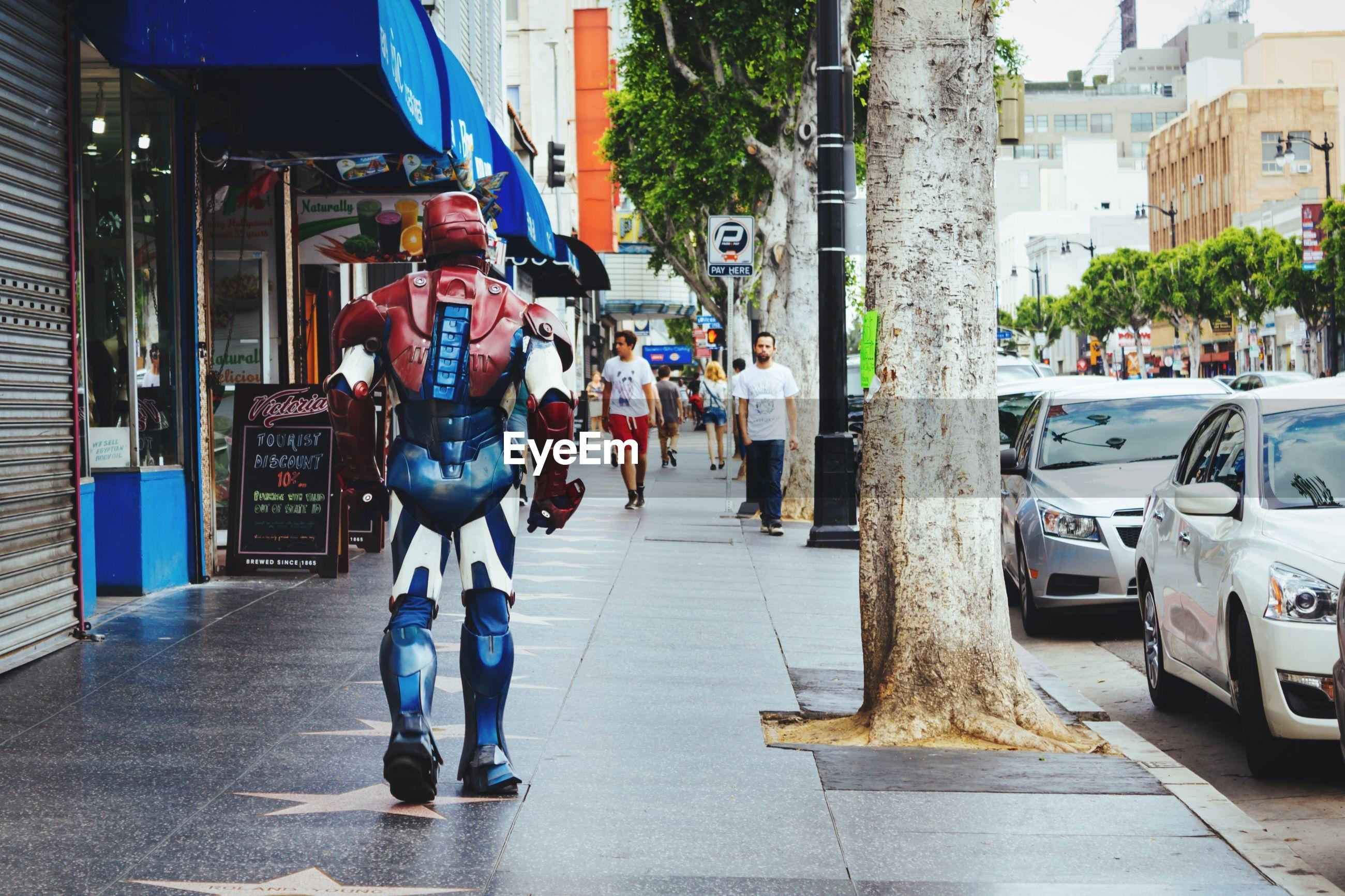 Rear view of man wearing metal costume while walking on sidewalk