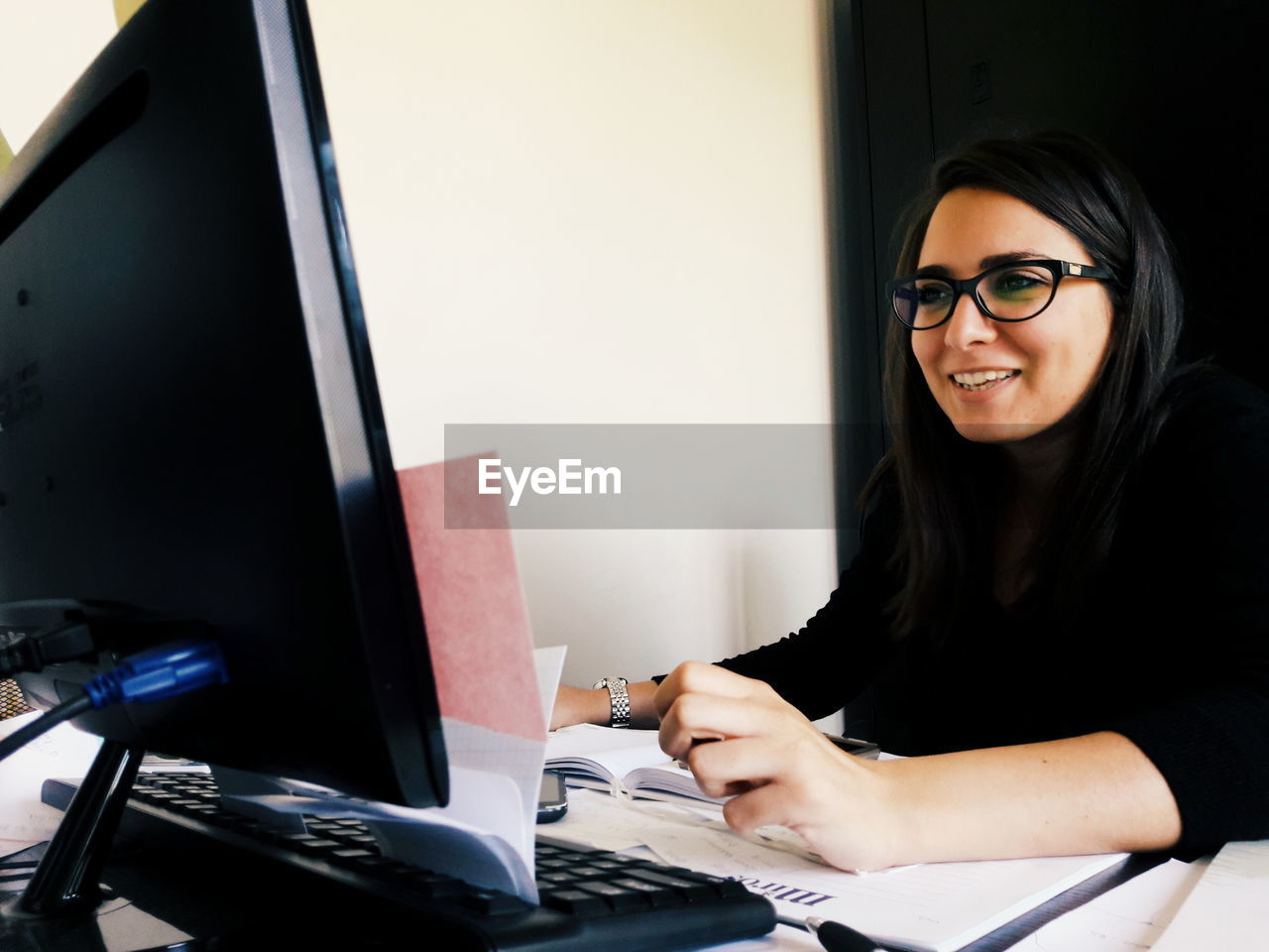 smiling, one person, eyeglasses, real people, technology, indoors, happiness, desk, computer monitor, computer, sitting, young adult, looking at camera, young women, cheerful, portrait, day, people