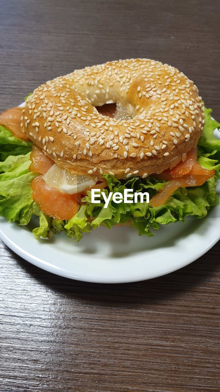 food, food and drink, ready-to-eat, freshness, sandwich, fast food, bread, burger, still life, table, unhealthy eating, indoors, lettuce, plate, no people, wood - material, close-up, serving size, vegetable, hamburger, snack, temptation