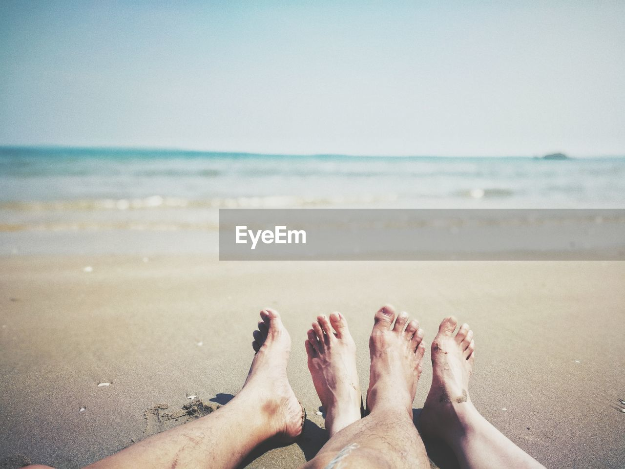 Low Section Of Couple Relaxing On Beach