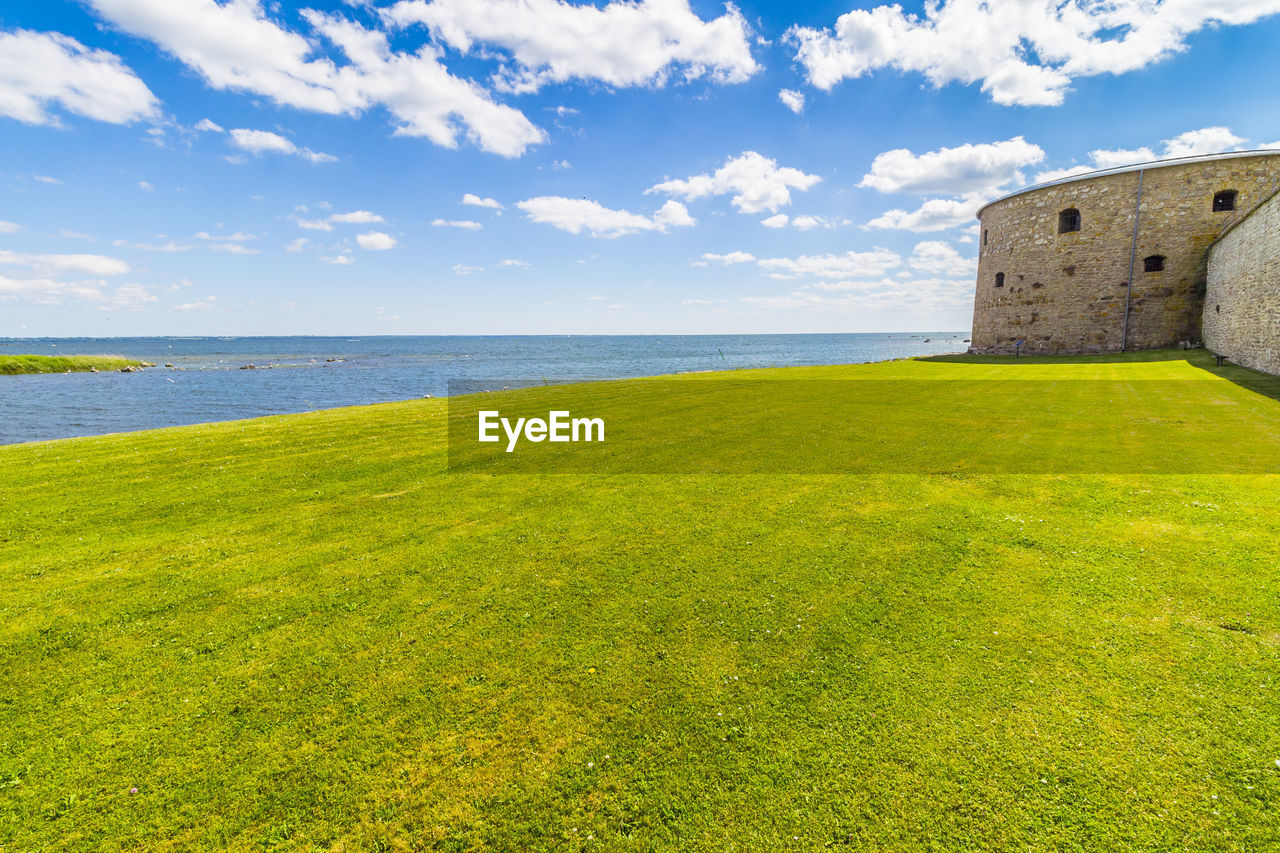Grassy field and historic building by sea against cloudy sky