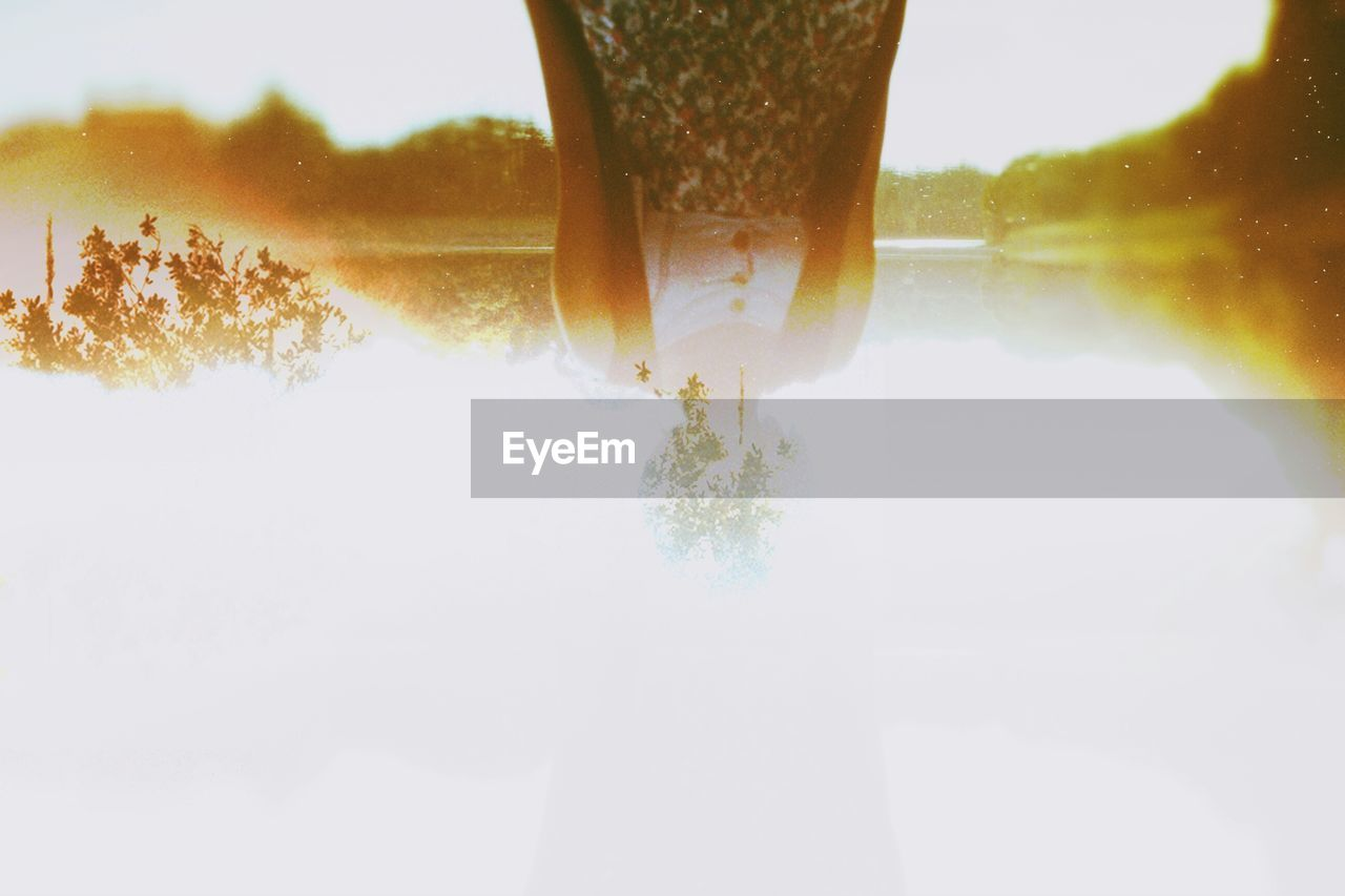 Multiple exposure of upside down woman with trees against sky