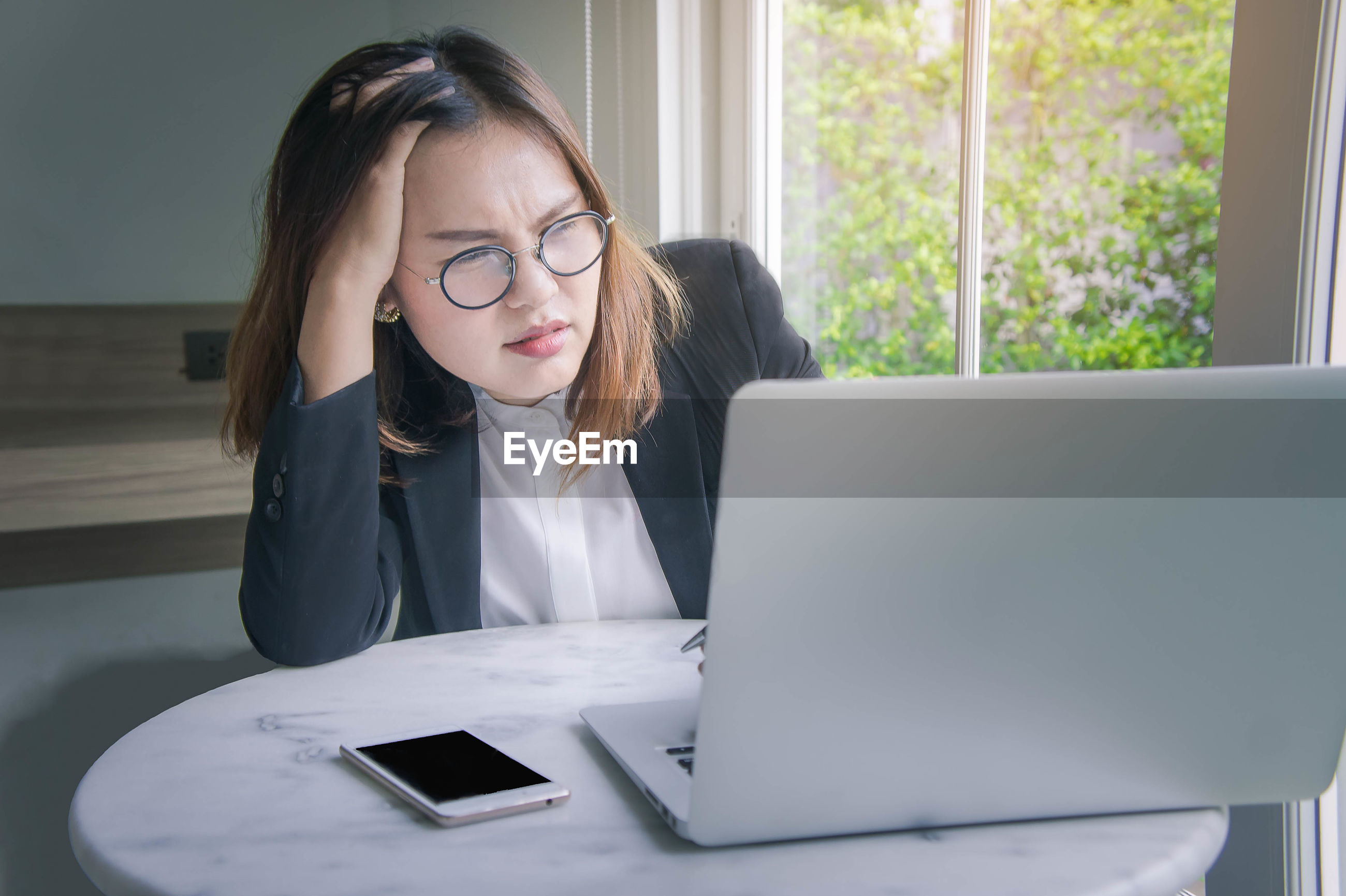 Tired businesswoman working on laptop in office