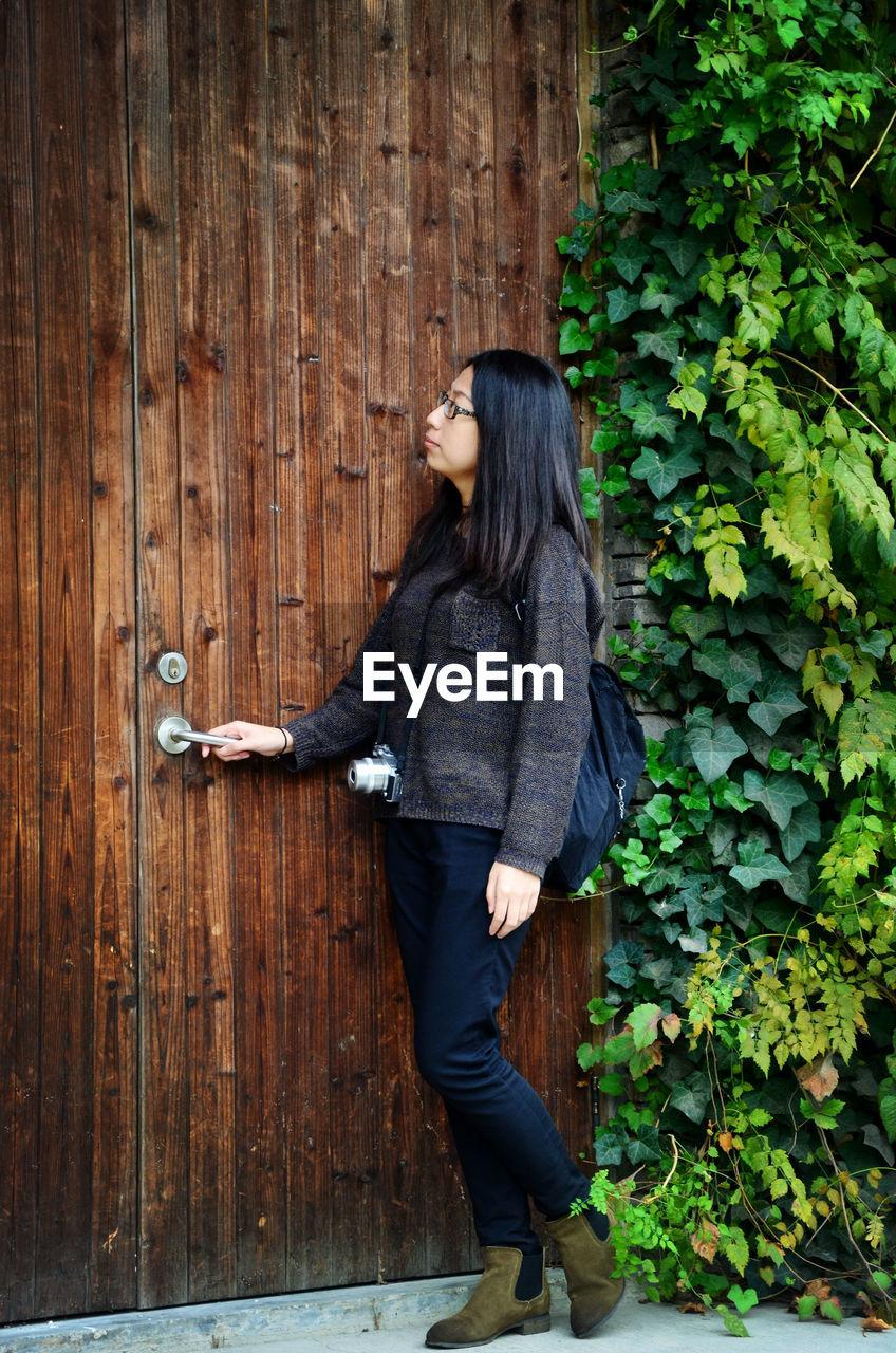 Young Woman Opening Wooden Door