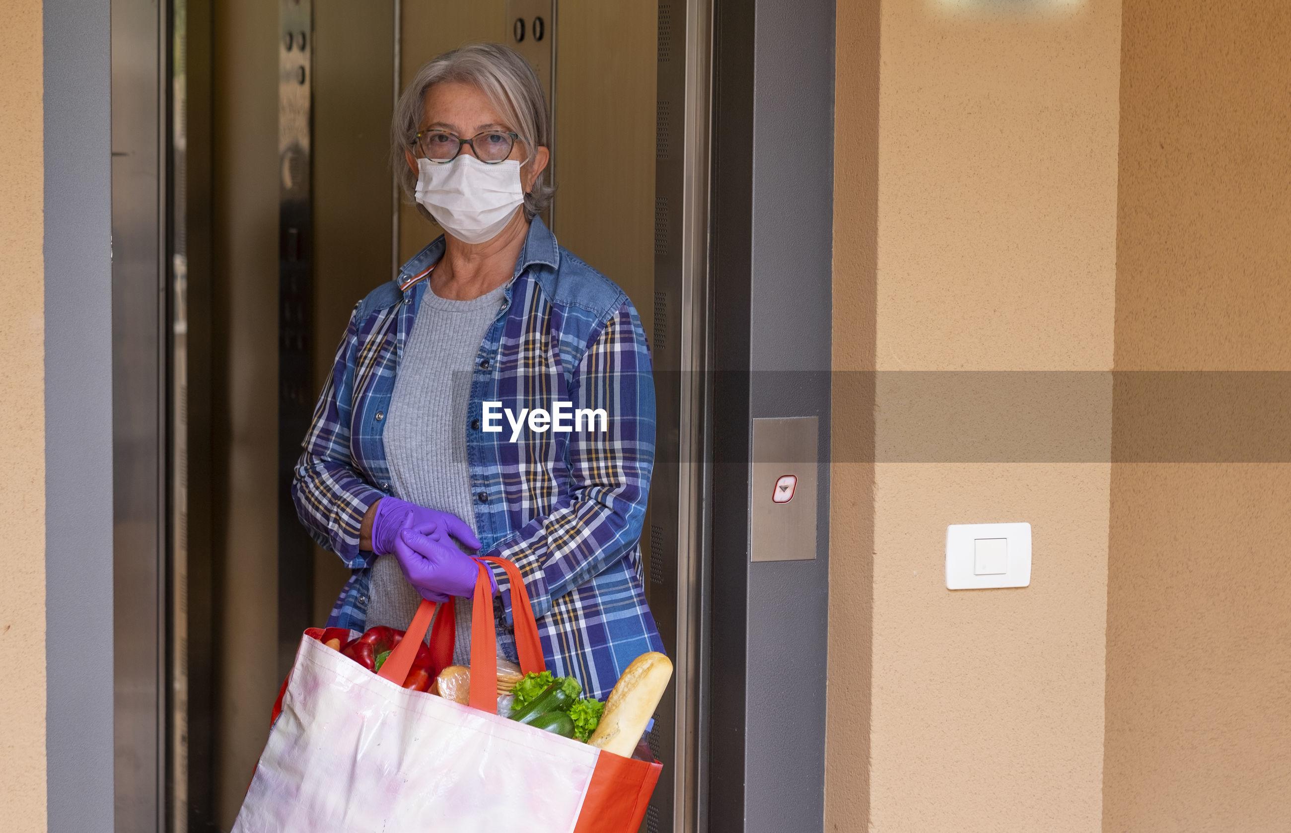 Portrait of senior woman standing on doorway