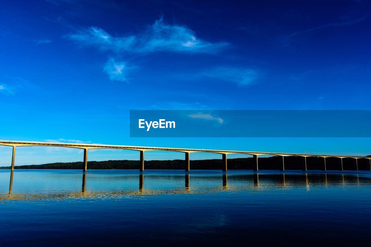 Bridge over calm blue sea against sky