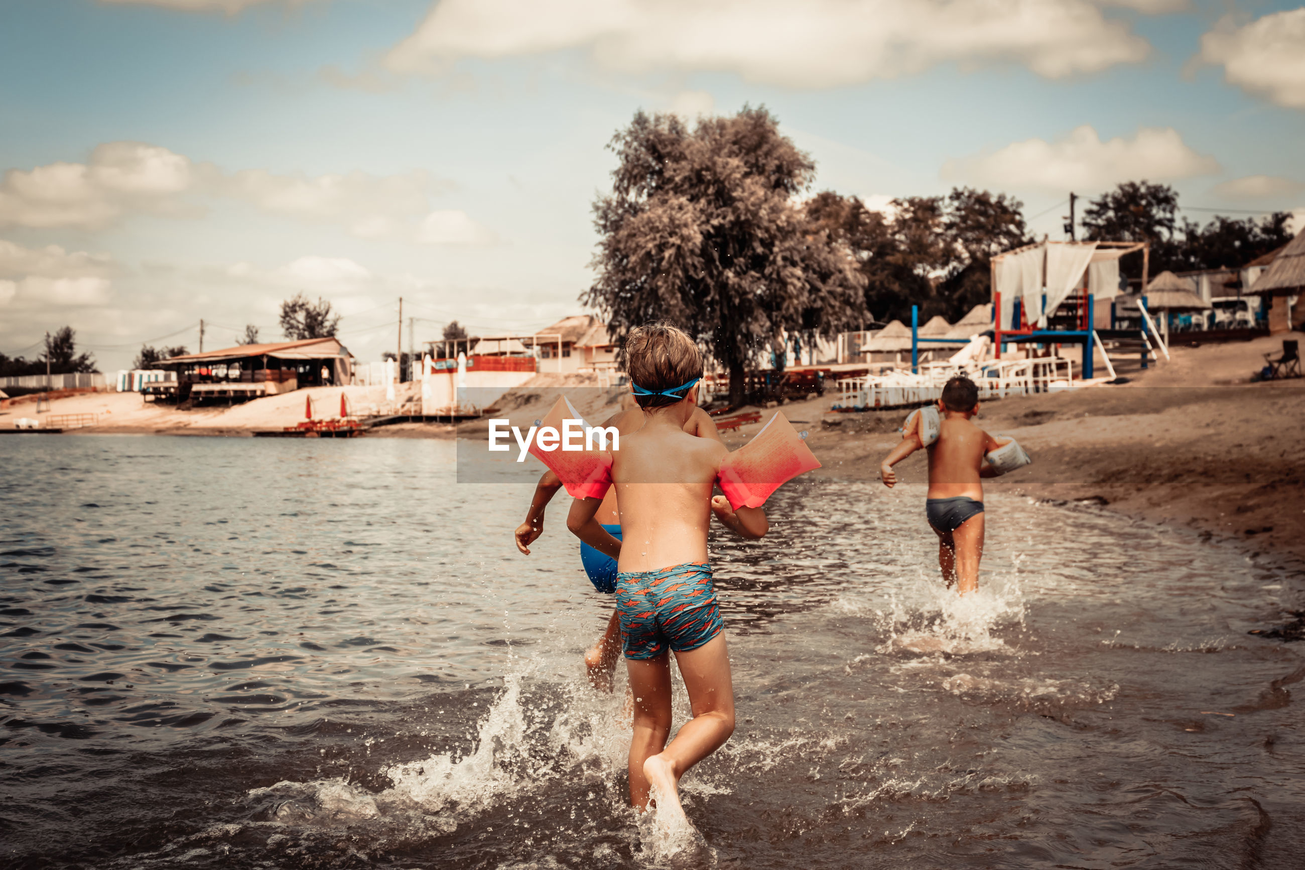 Rear view of boys having fun while running through sea in summer day.