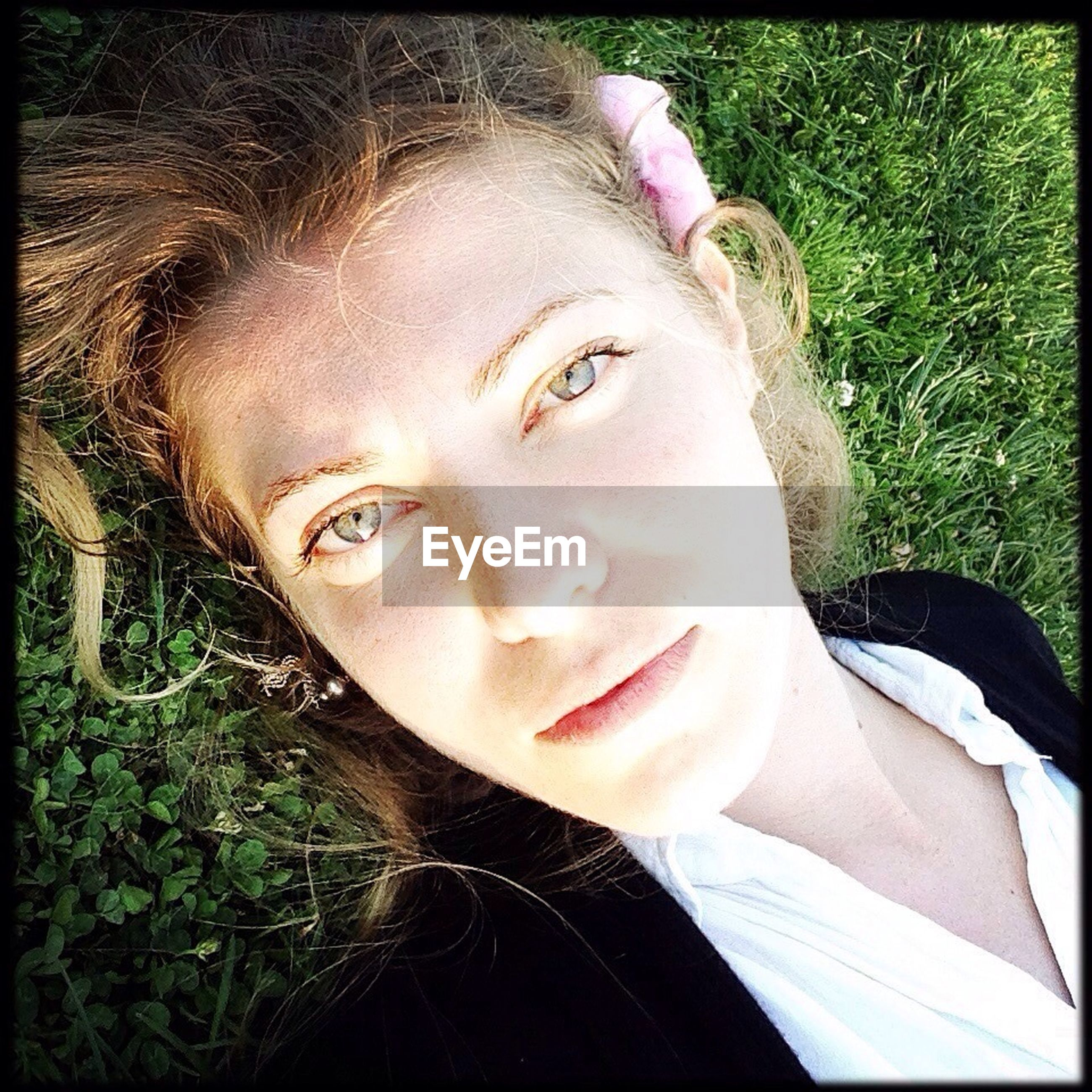 High angle portrait of beautiful young woman relaxing in park