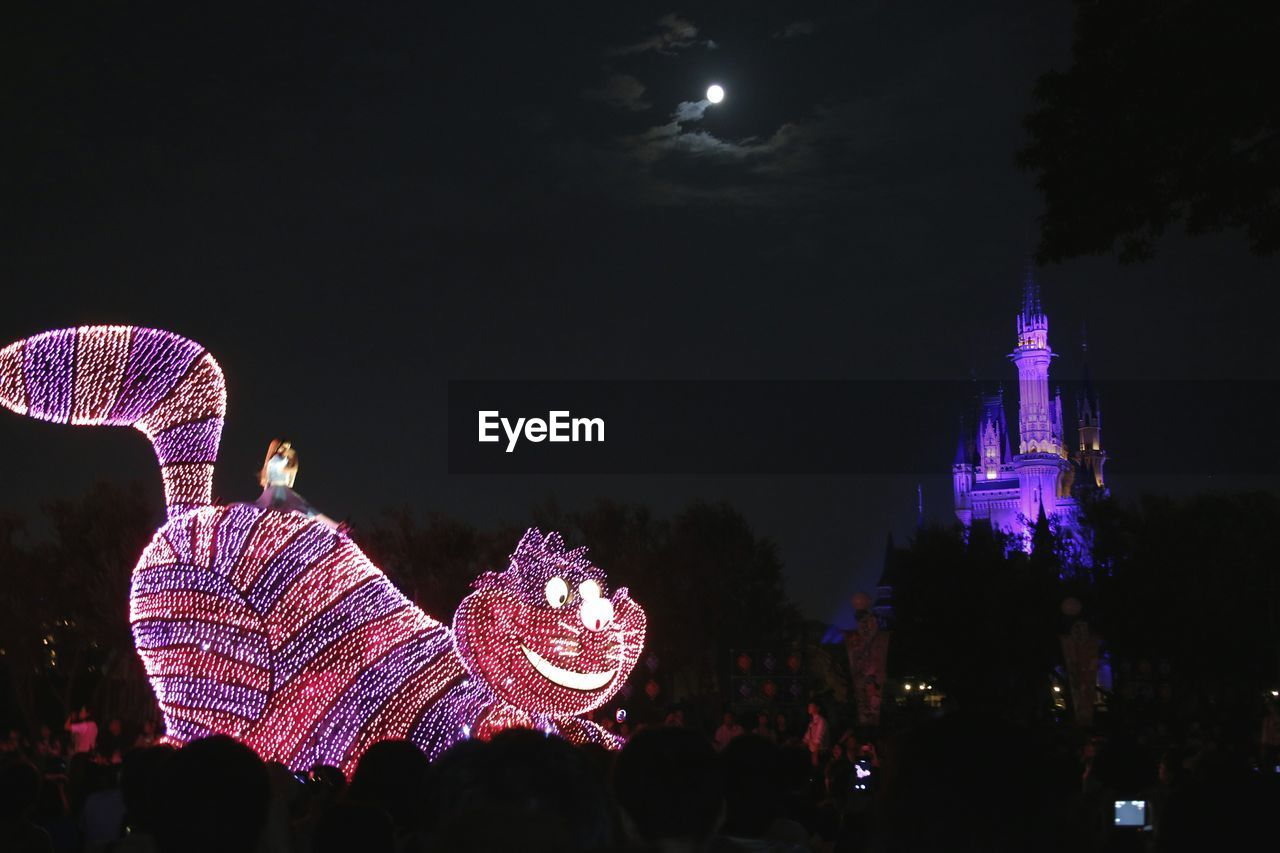 illuminated, night, sky, arts culture and entertainment, architecture, group of people, lighting equipment, incidental people, built structure, celebration, nature, amusement park, building exterior, low angle view, tree, outdoors, amusement park ride, city, decoration, festival
