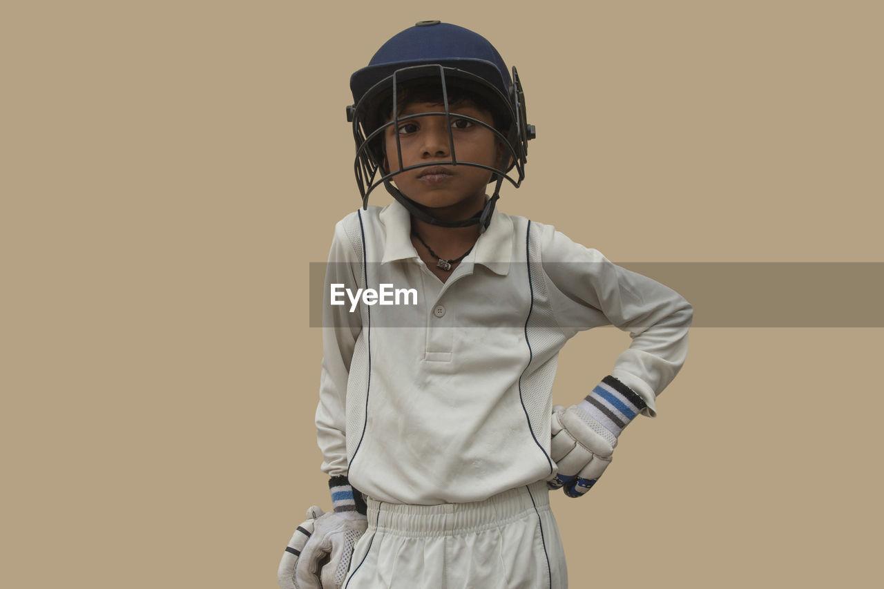 PORTRAIT OF BOY STANDING AGAINST ORANGE BACKGROUND