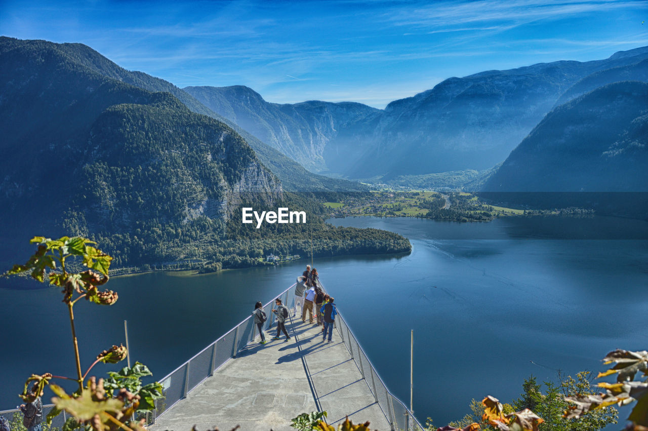 High Angle View Of People At Observation Point Over Lake Against Mountains