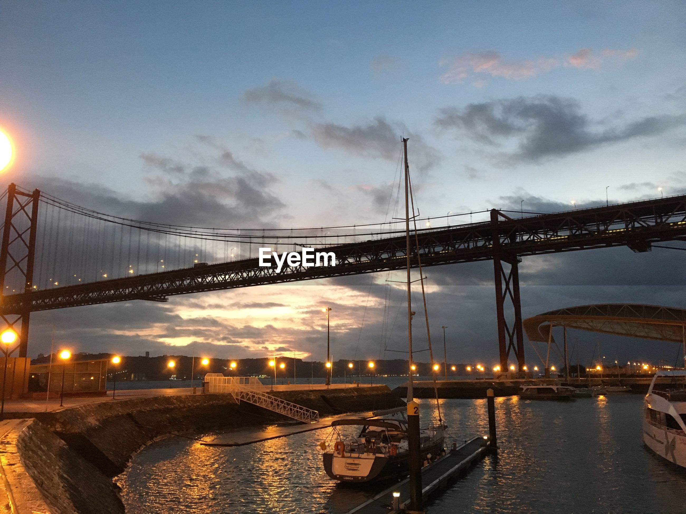 architecture, built structure, illuminated, water, reflection, sky, building exterior, waterfront, city, connection, night, dusk, river, lighting equipment, bridge - man made structure, cloud - sky, street light, travel destinations, outdoors, low angle view