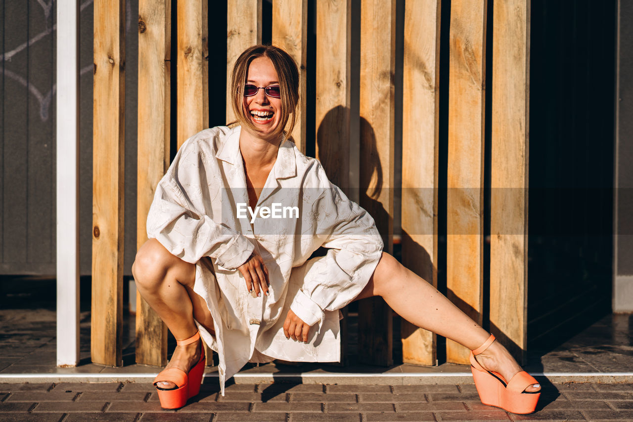 Portrait of young woman crouching against planks