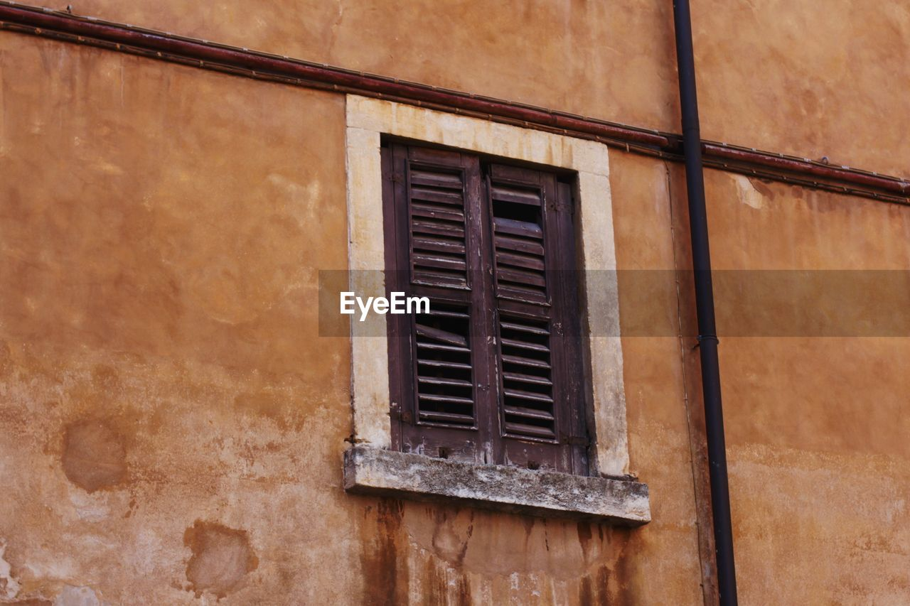 window, built structure, architecture, building exterior, building, no people, day, wall - building feature, residential district, low angle view, house, outdoors, old, brown, wall, weathered, close-up, metal, geometric shape, wood - material, window frame