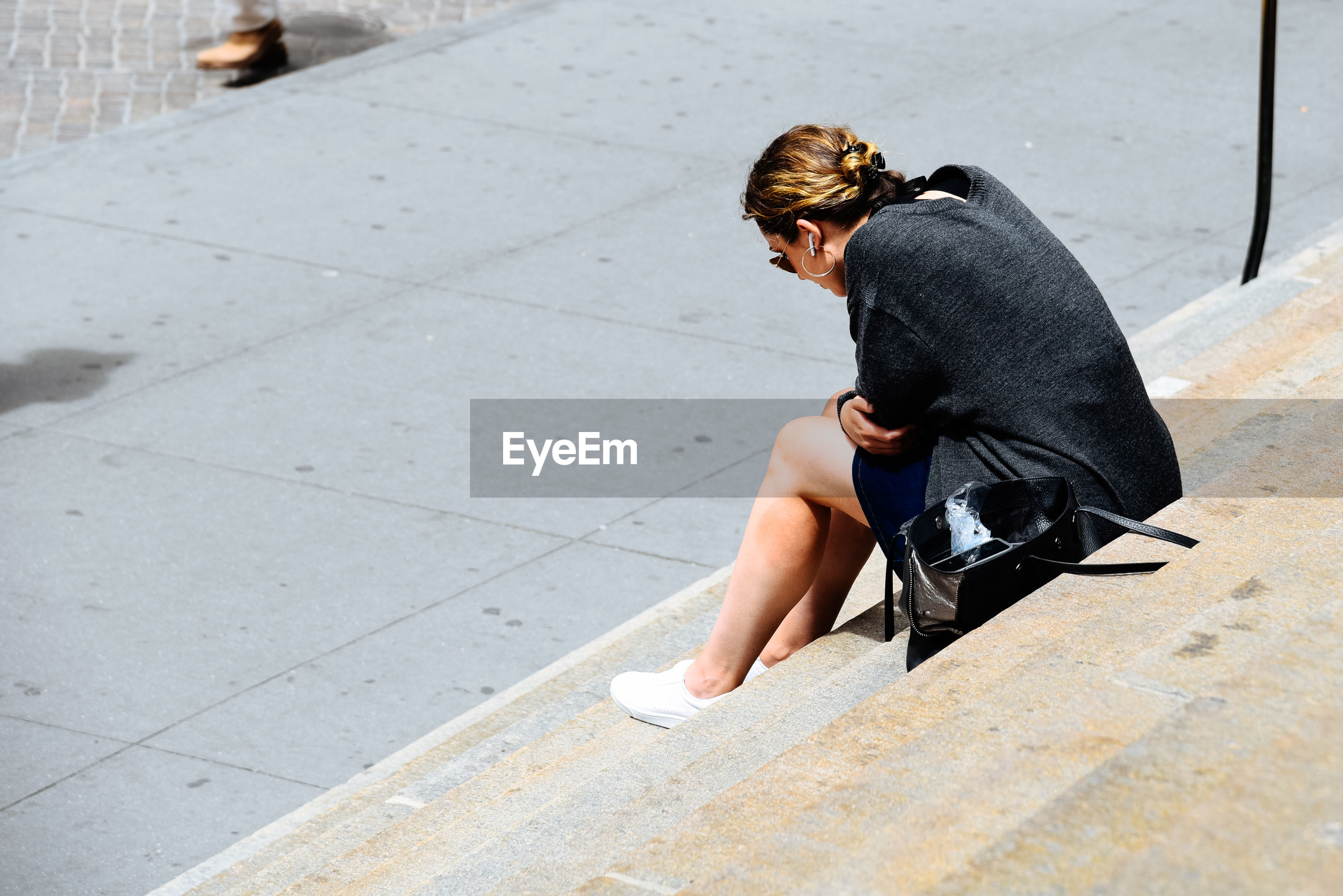 Side view of young woman sitting on steps during sunny day