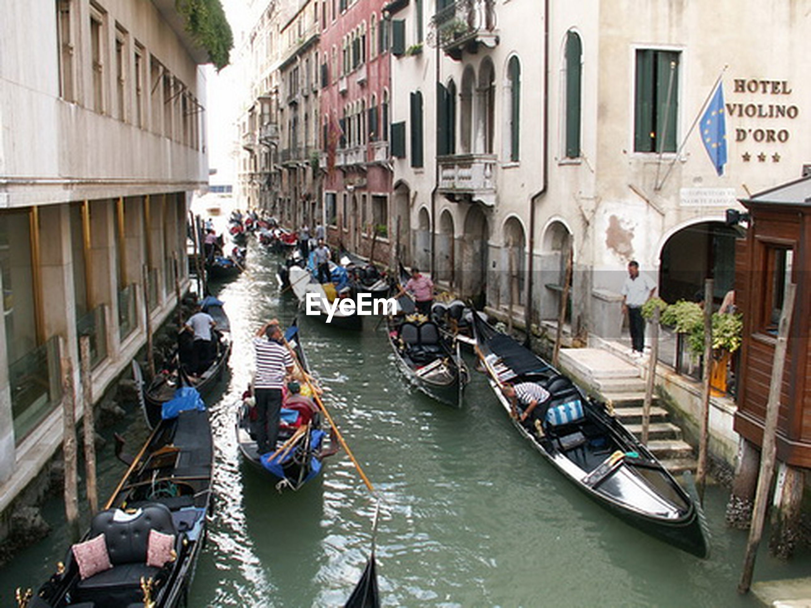 architecture, building exterior, built structure, canal, large group of people, transportation, water, mode of transport, person, men, city, city life, nautical vessel, street, boat, incidental people, building, travel, lifestyles